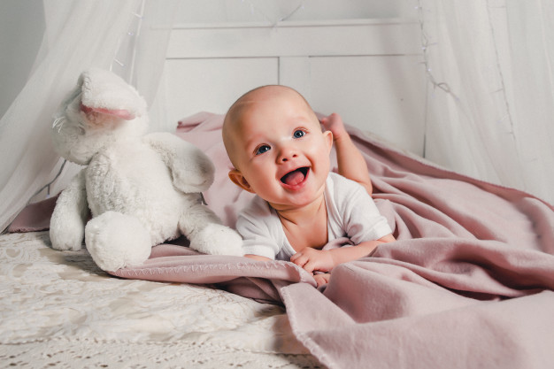 پرستار-کودک-کودک-کوچک-با-لبخندهای-خرگوش-اسباب-بازی-تختخواب-می-کند